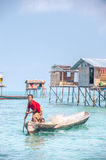 Sea Gypsy Woman paddling her sampan with her kids. Stock Images