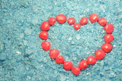 Sea heart. Heart  from pink shells on blue sea salt background Royalty Free Stock Photos