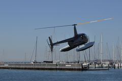 Sea helicopter tour take off. Sea helicopter take off. An amphibious helicopter is a helicopter that is intended to land in and take off from both land and water royalty free stock photography