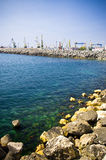 Sea horizon. With rocky shore and shipyard in the back plane Royalty Free Stock Images