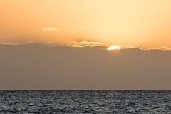 Sea horizon sunrise over low bank of cloud. Beautiful ocean scen. Ic. Seascape with copy space Stock Image