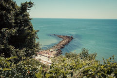 Sea III. A peek from a top of a hill overlooking a natural stone dock in the sea Stock Photography