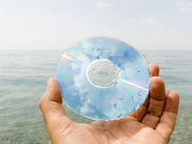 Sea imagination. Computer disk in a hand on seacoast in drops of water Royalty Free Stock Photo