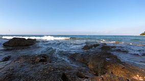 Sea incoming waves with foam washing rocky shore, sail, bird. Sea incoming waves with foam washing rocky shore, white sail far away, gull flying over water stock footage