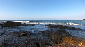 Sea incoming waves with foam washing rocky shore, white sail. Far away against blue clear sky. Oncoming sea waves with sea foam washing-down stone coast stock footage