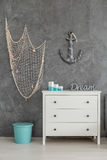 Sea inspired interior. With white commode, fishing net and anchor hanging on the wall Royalty Free Stock Photos