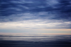 The sea with an island at the horizon Royalty Free Stock Photos