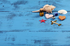 Sea items, hearts and plane on blue wooden background Stock Photography