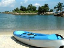 Sea Kayak on deserted beach. Tropical destination  : Singapore's Sentosa Island Beach with a canoe or kayak on the beach Royalty Free Stock Photos