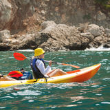 Sea kayak. A young female in a yellow kayak kayaking Royalty Free Stock Images