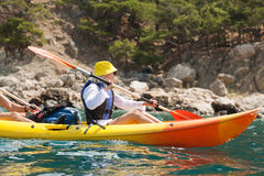 Sea kayak. A young female in a yellow kayak kayaking Stock Images