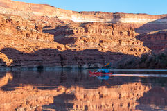 Sea Kayaking Canyonlands. Mature woman paddling glass calm Green River in Stillwater Canyon Royalty Free Stock Images