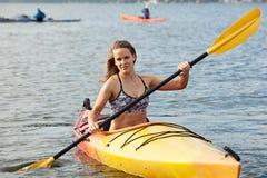 Sea kayaking. Young woman enjoying her sea kayaking adventure royalty free stock photos