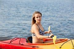 Sea kayaking. Young woman enjoying her sea kayaking adventure stock image