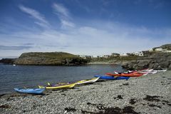 Sea Kayaks. Taking a rest on a stony beach Trearddur Bay Isle of Anglesey Royalty Free Stock Photo