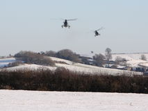 Sea Kings and Snow. A pair of Navy Sea Kings perfomr a low approach to a UK airfield against a Snowy backdrop stock photography