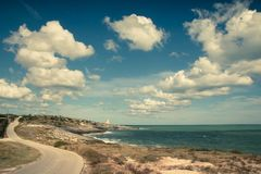 Sea landscape with blue sky and curvy winding coastal road. Vieste, Italy. Sea landscape, blue sky with white fluffy clouds, and curvy coastal road. Vieste Stock Photos