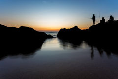 Sea landscape and fisherman stand on rock at beach with sunset t Royalty Free Stock Photography