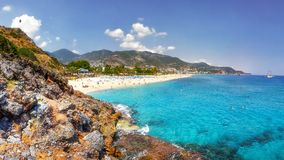 Sea landscape of the Mediterranean on clear sunny day. Sandy beach, rocks, blue sky, mountains and sea. Paradise Bay in Alanya. Tropical resort for summer Stock Photography