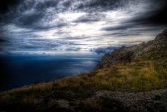 Sea landscape. Of the mountains and the sea with deep blue clouds before the storm Royalty Free Stock Photography