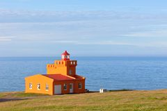 Sea Landscape with Orange Lighthouse and Blue Sky Stock Photo