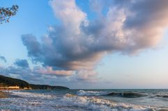 Sea landscape is a pebbly beach with waves in white foam. A beautiful sky with clouds, a warm summer day stock images