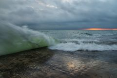 The sea landscape, raging waves at dawn,. The cloudy sky, a long exposure. Harsh sea. Black Sea. Wooden pier, water from the wave on the pier Stock Photo