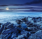 Sea landscape on the rocky coast at night. Calm sea landscape with some wave near rocky coast with boulders and seaweed at night in full moon light Royalty Free Stock Photos