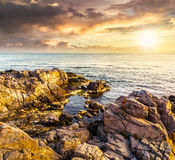 Sea landscape on the rocky coast at sunset. Calm sea landscape with some wave near rocky coast with boulders and seaweed  in evening light Stock Images