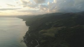 Sea landscape at sunset. Aerial view of seashore with beach and mountains with sky and clouds at sunset. Philippines, Luzon. View of the ocean with the stock footage
