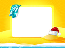 Sea landscape with towel and Christmas hat. On the sand and white space for text Royalty Free Stock Image