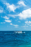 Sea landscape with a traditional Dhoni boat and the clouds, Mald. Sea landscape with a traditional Dhoni boat and the white clouds, Maldives Royalty Free Stock Photos