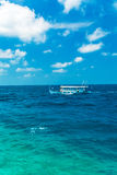 Sea landscape with a traditional Dhoni boat, Maldives. Sea landscape with a traditional Dhoni boat and the white clouds, Maldives Stock Photography