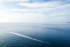 Sea landscape with wake of small fast motorboat Royalty Free Stock Image
