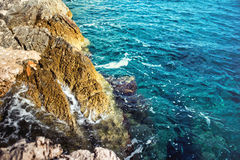 Sea landscape wallpaper background with island cliffs and ocean hitting rocks Stock Image