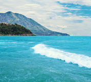 Sea landscape. Water waves running in the sea with mountains on the background Stock Image