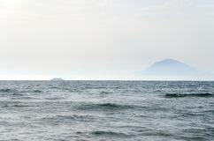 Sea landscape. Wavy sea, a ferryboat silhouette and high mountain as background Stock Images
