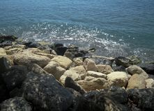 Sea landscape, white and black sea rocks and glitter wave. Royalty Free Stock Photos