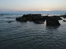 Sea and large rocks During the sunset. On natural background royalty free stock photos