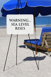 Sea Level Rises Warning. Sign at the ocean warning of the rising of sea levels due to global warming royalty free stock photos