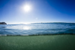 Sea Level. A water shot of a beautiful summer day with a portion submersed below water level. with surfers waiting for waves in the distance Royalty Free Stock Images