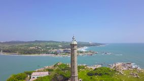 Sea light house on rocky island in blue sea and modern city on skyline deone view. Aerial landscape lighthouse tower on. Green island in ocean stock video