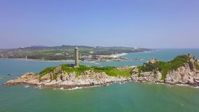 Sea light house on rocky island in blue sea and modern city on skyline, aerial landscape from drone. Scenic view. Lighthouse tower on green island in ocean stock video footage