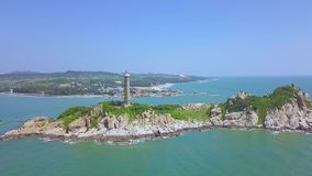 Sea light house on rocky island in blue sea and modern city on skyline, panoramic view from drone. Aerial view. Lighthouse tower on green island in ocean stock video footage