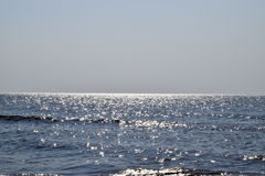 Sea line of the horizon. Sea and sky. The waves and glare of the sun are reflected from the waves of the sea. Seascape. Stock Photo