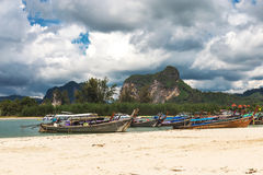 Sea, long tail boats, yachts and tropical forest. Stock Photography