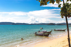 Sea, long tail boats, yachts and tropical forest. Stock Photos