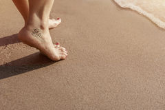 Sea lover Woman with tattoo walking on Sand beach during sunset. Or sunrise in summer, Closeup and Focus on female feet and red nail Royalty Free Stock Image