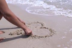Sea A mão fêmea tira um coração na areia Fotos de Stock