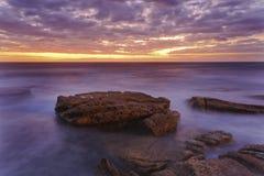Sea Maroubra Red stones. Rising sun over horizon from Maroubra beach in Sydney's pacific coast of Australia Stock Image